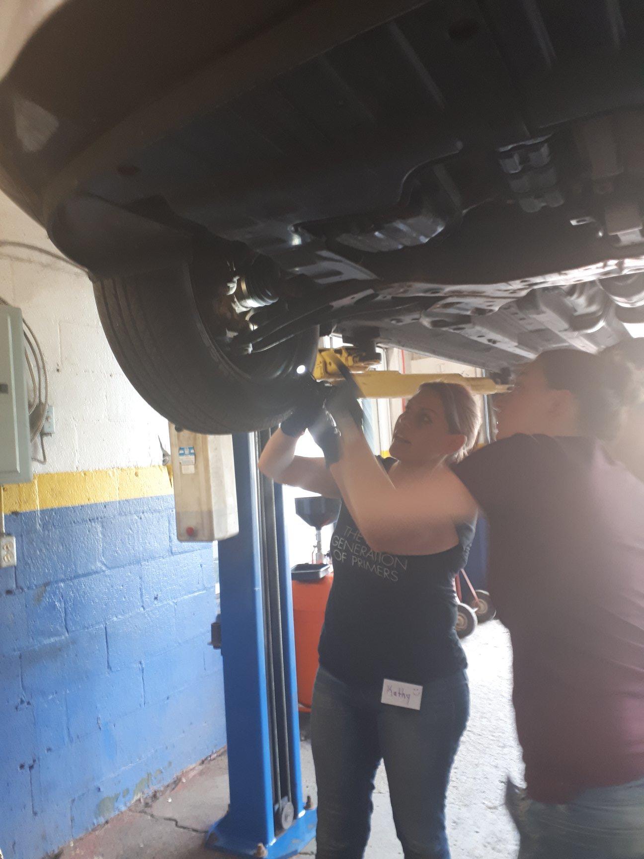 Two women working underneath a car